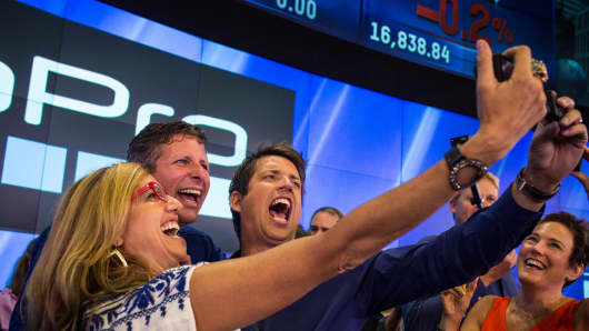 Nick Woodman (R), founder and CEO of GoPro takes pictures with co-workers during the company's IPO at the Nasdaq on June 26, 2014.