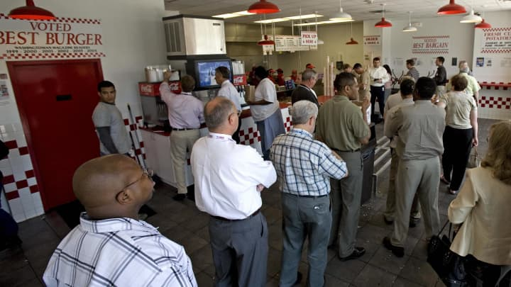Customers wait in line to place their food order at the Five Guys Famous Burgers and Fries restaurant in Washington, DC.