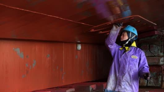 A worker prepares to inspect a fishing vessel under maintenance at the Kidoura Zosen K.K. shipyard in Miyagi Prefecture, Japan.