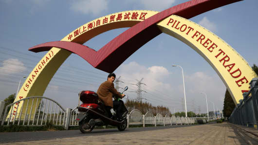 A man rides a motorcycle under a sign for the China (Shanghai) Pilot Free Trade Zone at a gate to the Waigaoqiao free trade zone and logistics park in Shanghai, China.