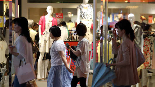 Pedestrians walk past a clothing store in Tokyo, Japan.