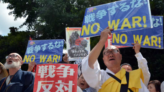 A Buddhist monk (R) holds a placard while joining other protesters as they shout slogans against the government of Japanese Prime Minister Shinzo Abe, Tokyo.