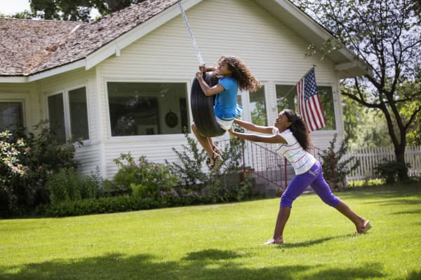Two sisters play on a tire swing in front of their house in Idaho.