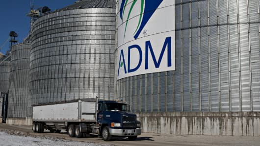 A truck passes in front Archer-Daniels-Midland signage displayed on the side of a grain storage bin at an ADM grain elevator in Niantic, Illinois.