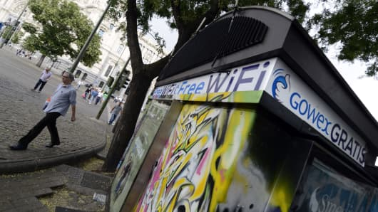 People walk past a kiosk with an advertisement for wifi provider Gowex in Madrid on July 3, 2014.