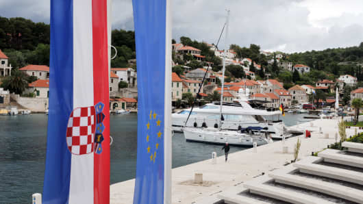 The Croatian national flag, left, sits alongside the European Union one