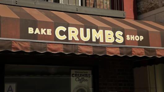 Signage for Bake Crumbs Shop Inc. is displayed on the awning above a store in New York. Crumbs Bake Shop Inc., the cupcake chain facing default on more than $14 million in loans, closed all of its stores yesterday after years of struggling to make money in a crowded market.