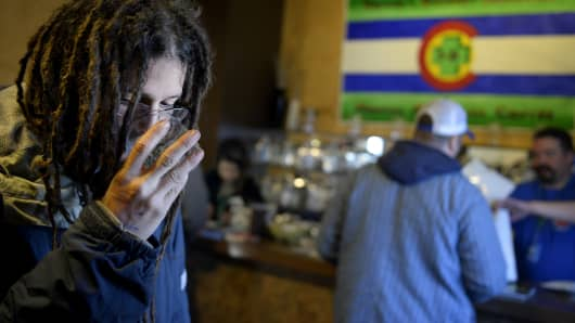 A patron smells a variety of marijuana at 3D Cannabis Center in Denver, CO.