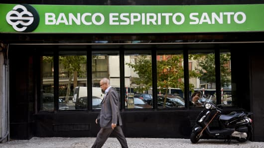 A man walks past the Espirito Santo Bank headquarters in Lisbon, Portugal.