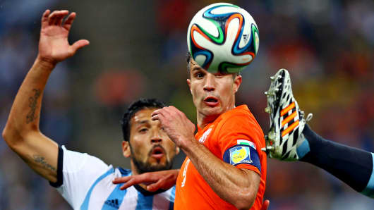 Robin Van Persie of the Netherlands and Ezequiel Garay of Argentina during the 2014 FIFA World Cup Brazil Semifinal match in Sao Paulo.