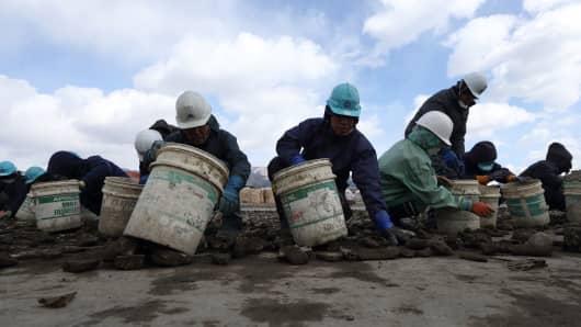 Workers sort through rocks at a construction site in Rikuzentakata, Iwate Prefecture, Japan.