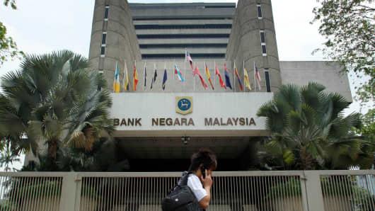 A pedestrian walks past the Bank Negara Malaysia headquarters in Kuala Lumpur, Malaysia.