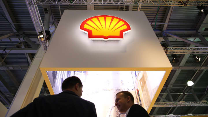 Attendees stand beneath a Shell logo at the Royal Dutch Shell corporate pavilion during the 21st World Petroleum Congress in Moscow.