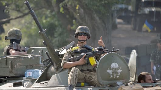 A Ukrainian serviceman sits atop an armored personnel carrier near the eastern Ukrainian city of Slavyansk.