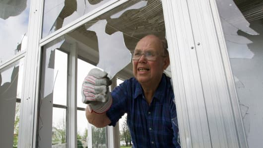 Lloyd Wright clears broken glass from his porch in Blair, Neb., June 4, 2014, following a severe storm that passed through the region the previous evening.