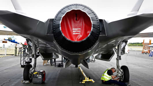 A worker checks the landing gear of a model of a F-35 Lightning II joint strike fighter jet, produced by Lockheed Martin Corp., as it stands on display prior to the opening of the Farnborough International Airshow in Farnborough, U.K., July 13, 2014.