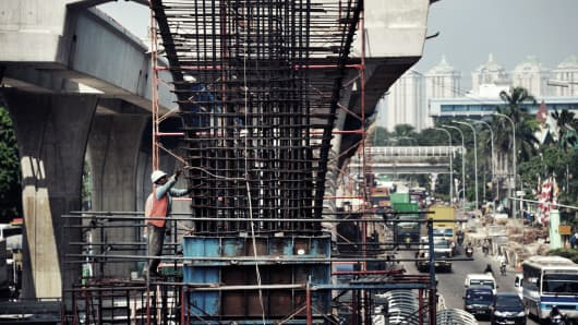 Laborers work on a construction site for a flyover n Jakarta, Indonesia.