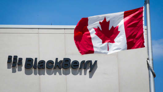 A Canadian flag is pictured in front of a Blackberry sign in Waterloo, Canada.