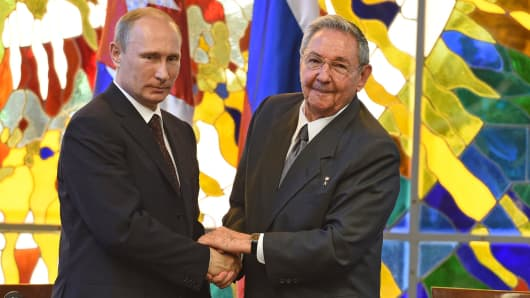 Russian President, left, greets Cuban President Raul Castro during an official visit at Revolution Palace in Havana, Cuba.