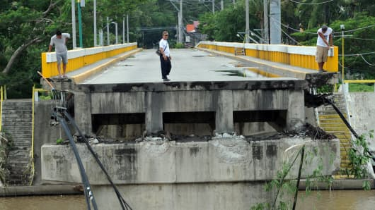 Residents survey a bridge destroyed at the height of typhoon Ammasun in, Batangas City, southwest of Manila, Indonesia.
