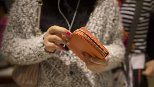 A shopper looks at a Furla SpA wallet inside a Furla store in Hong Kong, China, on Thursday, Feb. 6, 2014.