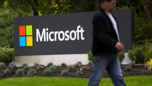 A pedestrian walks past the Microsoft campus in Redmond, Wash.