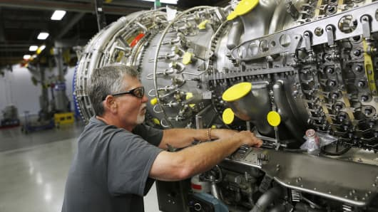 A mechanic works to hang a gearbox on a CF6-80C2 jet engine at General Electric's GE Aviation factory in Cincinnati, Ohio.