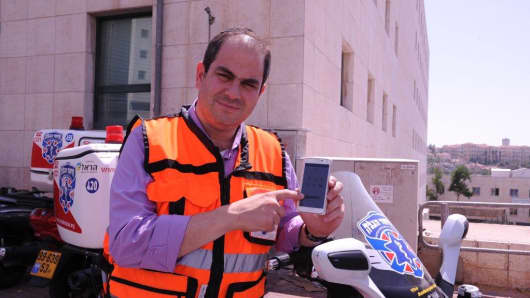"Eli Beer, founder of United Hatzalah, with ""SOS"" emergency response app"