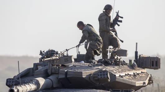 Israeli soldiers stand on their Merkava tank on july 17, 2014 at an army deployment area near Israel's border with the Gaza Strip.