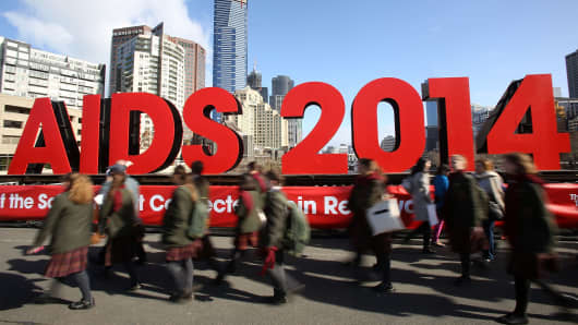 Members of the public walk past signage on the Princes Bridge for the 20th International AIDS Conference on July 18, 2014 in Melbourne, Australia.