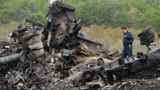 Rescuers stand on the site of the crash of Malaysia Airlines Flight MH17.