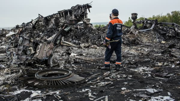 An emergency services worker photographs debris from a Malaysia Airlines plane crash in Grabovka, Ukraine.