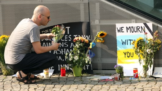 A visitor places flowers at a temporary memorial for the 298 victims of shot down Malaysian jetliner Flight MH17 from Amsterdam to Kuala Lumpur.