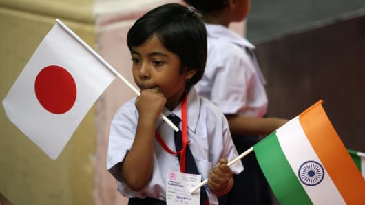 An Indian schoolgirl hold the national flags of India and Japan.