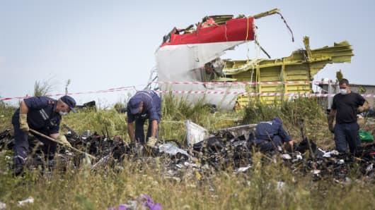 Ukrainian rescue servicemen look through the wreckage of Malaysia Airlines flight MH17 in Grabovo, Ukraine.