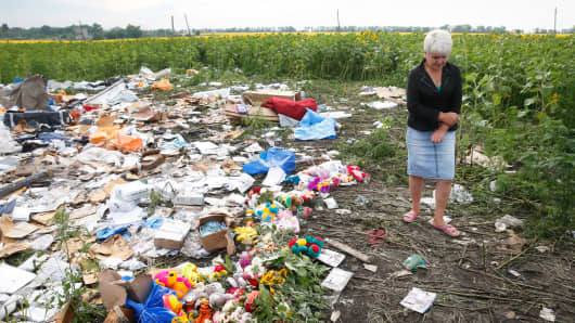 A local resident stands near flowers and mementos placed at the crash site of Malaysia Airlines Flight MH17, near the settlement of Rozspyne in Donetsk.