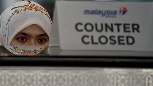 A Malaysia Airlines employee sits behind a closed ticket counter at the Kuala Lumpur International Airport in Sepang.