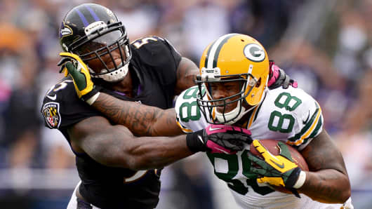 Jermichael Finley No. 88 of the Green Bay Packers stiff arms Terrell Suggs No. 55 of the Baltimore Ravens on October 13, 2013 in Baltimore, Maryland.