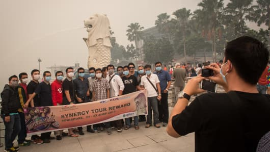 A tour group wearing masks poses for a photograph in front of the haze covered skyline on June 2013 in Singapore.