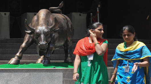 Indian office workers walk past the bronze bull outside the Bombay Stock Exchange
