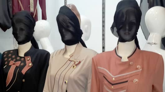 In this Monday, July 21, 2014 photo, mannequins with their faces covered are displayed in a shop window in central Mosul, 225 miles (360 kilometers) northwest of Baghdad, Iraq. The Islamic State group ordered clothes shop owners to cover the faces of the mannequins in Mosul, the shop owners said, apparently in line with strict interpretations of Shariah law that forbid statues or artwork depicting the human form.