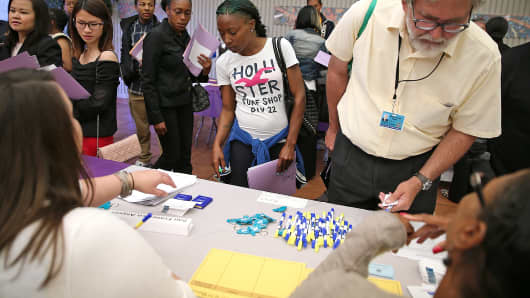 Job seekers wait to meet with a recruiter during a career fair in San Francisco.