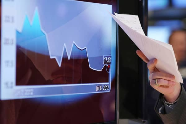 A television host points to a graph on a screen at the New York Stock Exchange in New York.