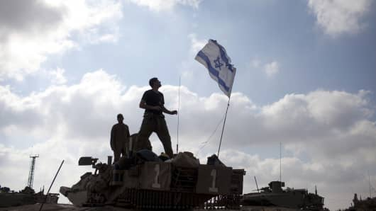 Israeli soldiers prepare their Tanks in a deployment area on July 24, 2014 on Israel's border with the Gaza Strip.