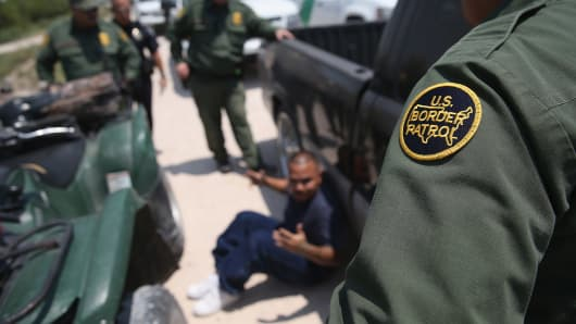 Border Patrol agents detain a suspected smuggler after he allegedly transported undocumented immigrants across the Rio Grande, from Mexico into the United States, in Mission, Texas.