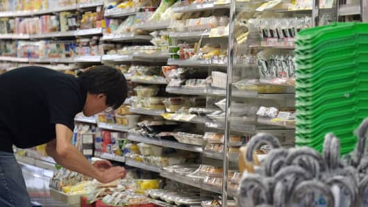 A storekeeper arranges products displayed at FamilyMart Co. convenience store in Tokyo, Japan.