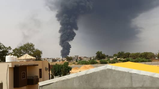 A picture taken on July 28, 2014 shows smoke billowing from an oil depot where a huge blaze started following clashes around Tripoli airport, Libya.
