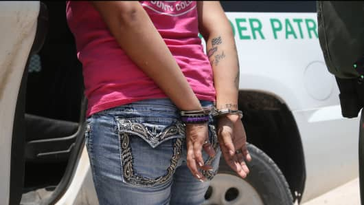 U.S. border patrol agents detain a suspected smuggler in Mission, Texas, after she allegedly transported undocumented immigrants who crossed the Rio Grande from Mexico into the United States on July 24, 2014.