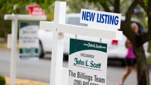 Signs stand in front of a house for sale in Seattle, Washington.