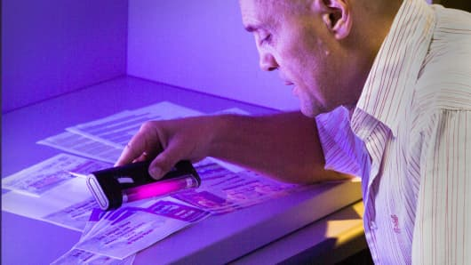 Xerox scientist Reiner Eschbach demonstrates how an ultraviolet light can reveal hidden words and figures.